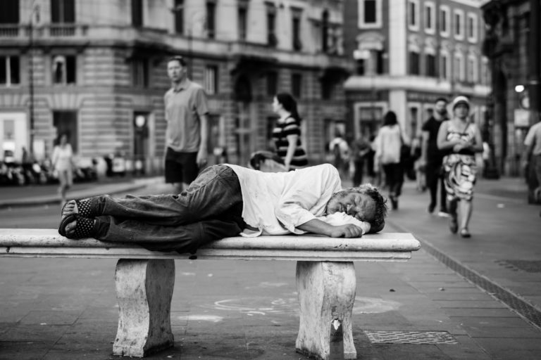 Un homme dors sur un banc